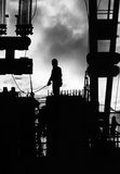Construction workers outdoors. Black and white photo of construction workers backlit by the setting sun creating a silhouette of them and their work site royalty free stock photography
