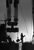 Construction workers outdoors. Black and white photo of construction workers backlit by the setting sun creating a silhouette of them and their work site stock images