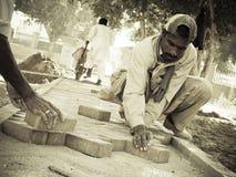 Construction Workers in Pakistan. Construction workers are making bricks floor, in Karachi,Pakistan Stock Photo