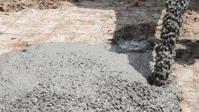 Construction workers pour concrete mix from cement mixer