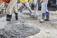 Construction workers pouring cement on road. Men levelling newly poured road concrete mix Stock Photography