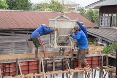 Construction workers pouring cement to creating beam to build a Stock Image