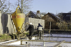 Construction workers pouring. Two male construction workers operating a concrete funnel for pouring cement into a form becoming the foundation of a new house Stock Photo