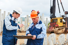 Construction workers with project in front of pile driver machine Stock Photography