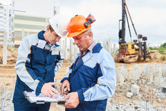 Construction workers with project in front of pile driver machine Stock Images