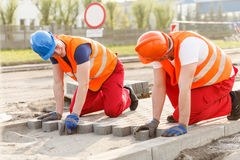 Construction workers putting paving stones Royalty Free Stock Photo