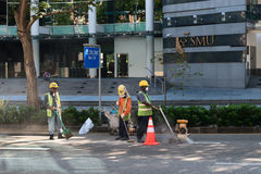Construction workers repair pavement on a downtown street. Royalty Free Stock Image