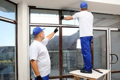 Construction workers repairing window. In house royalty free stock photo