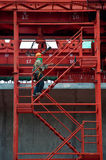 Construction workers on a scaffold ladder. Stock Images