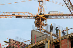 Construction workers on a scaffolding. Construction site with crane. New residental house construction Stock Image