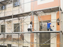 Construction workers in scaffolding of the old building facade for restore and renovate. Royalty Free Stock Photo