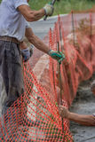 Construction workers set orange safety fence. Safety Orange Plastic Barrier Fence installation. Selective focus and motion blur Royalty Free Stock Images