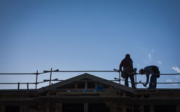 Construction Workers Silhouette on Roof Stock Photography