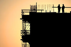Construction workers silhouettes at sunset. Construction workers silhouettes on a construction site at sunset stock image
