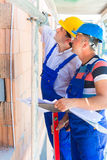 Construction workers on site checking quality Royalty Free Stock Photos
