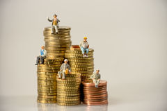 Construction workers sitting on money coin piles. Stock Photos