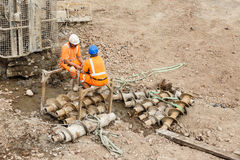 Construction workers sitting next to a pile drilling machine on a railway side site Stock Photography