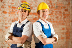 Construction workers standing with folded arms. Two construction workers standing in a construction site in front of a war brick wall. Their arms are folded and Stock Photography
