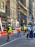 Construction Workers Stop Traffic, NYC, NY, USA. Construction workers stand in the street effectively holding traffic while a crane pulls a large piece of Royalty Free Stock Photography