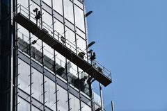 Construction workers on a suspended platform on a skyscraper. Glass facade royalty free stock photos