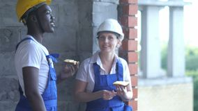 Construction workers take a break eating a sandwich and chatting. Professional shot in 4K resolution. 104. You can use it e.g. in your commercial video stock video footage