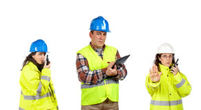 Construction workers talking with a walkie talkie. Three construction workers talking with a walkie talkie over a white background. Focus at front Stock Photos