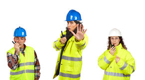 Construction workers talking with a walkie talkie. Three construction workers talking with a walkie talkie over a white background. Focus at front Royalty Free Stock Photo