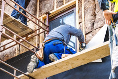 Construction workers thermally insulating house facade with glass wool. Royalty Free Stock Photos