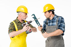 Construction workers with tools. Two male construction workers fighting with tools and looking at each other Stock Images