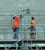 Construction Workers. Two construction workers at the work place wearing orange shirts and helmets Royalty Free Stock Photos