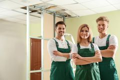 Construction workers in uniforms. Home repair service. Construction workers in uniforms indoors. Home repair service royalty free stock photography