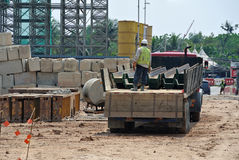 Construction workers unloading the sheet pile cofferdam of the lorry at a construction site Stock Images