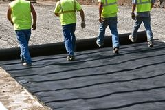 Free Construction Workers Unroll A Tarpaulin On A New Road Royalty Free Stock Photos - 161771378
