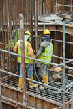Construction Workers Using Concrete Vibrator to compact the concrete Stock Image