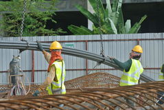 Construction workers using crane to lifting heavy reinforcement bar Royalty Free Stock Photos