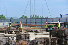 Construction workers using crane to lifting heavy reinforcement bar Stock Photo