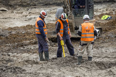 Construction workers using magnetic locator Stock Images