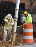 Construction workers vacuum mud from drainage pipe royalty free stock images