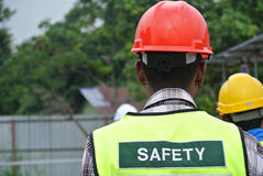 Construction Workers Wear Safety Vest Has Safety Sign On It. Royalty Free Stock Photo