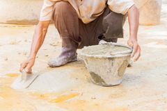 Construction workers were plastering repair floor in workplace build a house. Select focus bucket mortar with copy space add text stock images