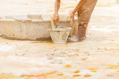 Construction workers were plastering repair floor in workplace build a house. Select focus bucket mortar with copy space add text stock photo