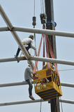 Construction workers working on the roof with construction worke. R standing in the mobile crane bucket Stock Photography