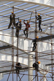 Construction workers working on scaffolding Stock Photos