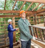 Construction Workers Working In Timber Cabin At. Male construction workers carrying ladder and wooden planks in timber cabin at site Royalty Free Stock Photo