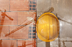 Construction workers yellow hard hat hanging on concrete wall Stock Photos