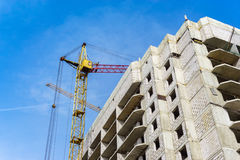 Construction with working crane at background of blue sky, development of modern Royalty Free Stock Photos