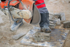 Construction. Working Power cutters cut paving tile cement dust boots form overalls stock photos
