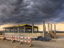 Construction works on a stormy sky. Building under construction with a stormy sky as background Royalty Free Stock Image