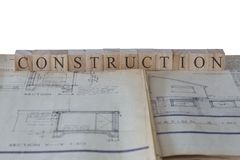 Construction written on wooden blocks on house extension building plans blueprints. With a white background stock photo