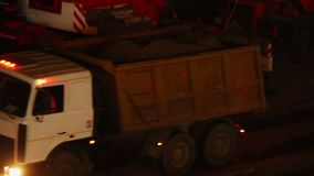 Construction yard trucks drive, working machines, night site. Stock footage stock footage